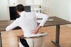 Uomo d'affari che soffre dal mal di schiena allo scrittorio Fotografia Stock Libera da Diritti