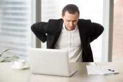 Uomo d'affari che soffre dal mal di schiena nel luogo di lavoro Immagine Stock Libera da Diritti