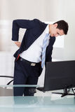 Uomo d'affari che soffre dal mal di schiena in ufficio Fotografia Stock Libera da Diritti
