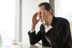 Uomo d'affari che soffre dall'emicrania o dall'emicrania Immagini Stock Libere da Diritti