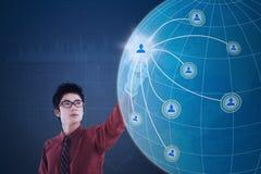 Uomo d'affari che sollecita il sociale dell'icona sul globo fotografie stock libere da diritti