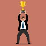 Uomo d'affari che sostiene un trofeo di conquista Fotografia Stock