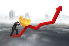 Uomo d'affari che spinge euro al punto di partenza del grafico di tendenza con la città Immagine Stock