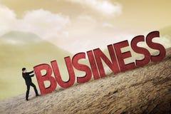 Uomo d'affari che spinge parola di affari 3D in salita Fotografia Stock