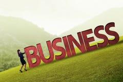 Uomo d'affari che spinge parola di affari 3D in salita Fotografia Stock Libera da Diritti