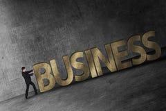 Uomo d'affari che spinge parola di affari 3D in salita Immagine Stock Libera da Diritti