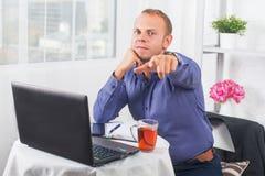 Uomo d'affari che ssitting sulla tavola e sui punti, ordine di elasticità Immagini Stock