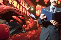 Uomo d'affari che sta accanto alla sua automobile alla lettura di notte, lanterne rosse nei precedenti immagine stock libera da diritti