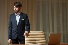 Uomo d'affari che sta al desktop Immagine Stock