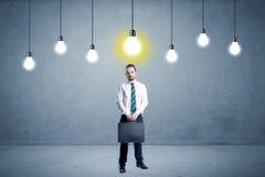 Uomo d'affari che sta banale con le lampadine qui sopra Fotografie Stock Libere da Diritti