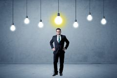 Uomo d'affari che sta banale con le lampadine qui sopra Fotografia Stock