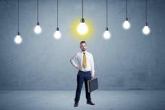 Uomo d'affari che sta banale con le lampadine qui sopra Fotografia Stock Libera da Diritti