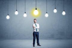 Uomo d'affari che sta banale con le lampadine qui sopra Fotografie Stock