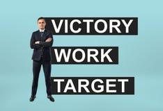 Uomo d'affari che sta con confidenza con un motto & un x27; target& x27 del lavoro di vittoria; dietro lui immagine stock