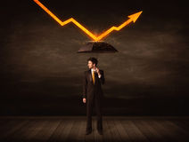 Uomo d'affari che sta con l'ombrello che tiene freccia arancio Immagini Stock