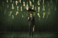 Uomo d'affari che sta con l'ombrello nel concetto della pioggia della banconota in dollari Fotografia Stock