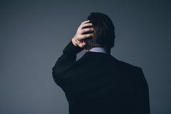 Uomo d'affari che sta con la sua mano alla sua testa fotografia stock libera da diritti