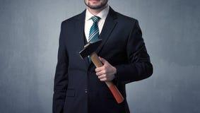 Uomo d'affari che sta con lo strumento sulla sua mano Fotografie Stock