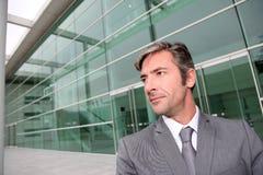 Uomo d'affari che sta davanti all'edificio per uffici Immagini Stock