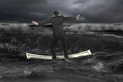 Uomo d'affari che sta equilibrante sul crogiolo di soldi che galleggia in Oc scuro Fotografia Stock Libera da Diritti