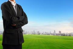 Uomo d'affari che sta il cielo blu vicino del campo di erba con il grattacielo Fotografia Stock Libera da Diritti