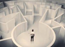 Uomo d'affari che sta nel centro del labirinto Immagine Stock