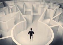Uomo d'affari che sta nel centro del labirinto Fotografia Stock Libera da Diritti