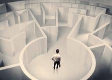 Uomo d'affari che sta nel centro del labirinto Fotografia Stock