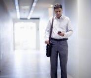 Uomo d'affari che sta nel corridoio e che esamina giù il suo telefono immagini stock