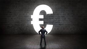 Uomo d'affari che sta nel euro-simbolo anteriore di un portale Immagini Stock Libere da Diritti