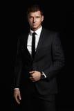 Uomo d'affari che sta sul fondo nero Giovane bello in vestito Fotografia Stock