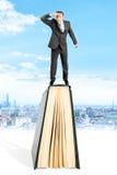 Uomo d'affari che sta sul libro e sul distogliere lo sguardo Immagine Stock
