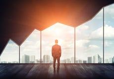 Uomo d'affari che sta sul pavimento di nuovo noi che guardiamo attraverso la grande finestra con paesaggio urbano ed il tramonto  Immagini Stock Libere da Diritti