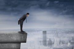 Uomo d'affari che sta sul tetto e sullo sguardo giù Fotografie Stock