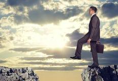 Uomo d'affari che sta sull'orlo della lacuna della roccia Fotografia Stock Libera da Diritti