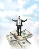 Uomo d'affari che sta sulla cima della pila del dollaro con un pacco attraversato di soldi Immagine Stock Libera da Diritti