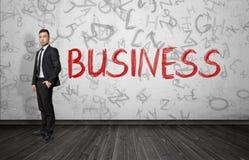 Uomo d'affari che sta vicino alla parola rossa & a x27; Business& x27; Immagine Stock