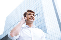 Uomo d'affari che stading vicino al grattacielo e che parla sul telefono cellulare fotografia stock libera da diritti