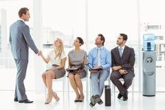 Uomo d'affari che stringe le mani con la donna oltre all'intervista aspettante della gente immagine stock libera da diritti