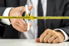 Uomo d'affari che taglia corda gialla Fotografia Stock