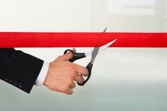 Uomo d'affari che taglia nastro rosso con le forbici Immagini Stock