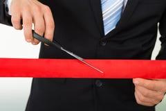 Uomo d'affari che taglia nastro rosso con le forbici Immagini Stock Libere da Diritti