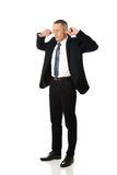 Uomo d'affari che tappa le sue orecchie Fotografia Stock Libera da Diritti