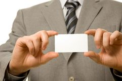 Uomo d'affari che tiene biglietto da visita in bianco con entrambi Immagini Stock