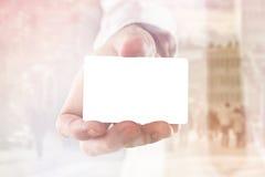 Uomo d'affari che tiene biglietto da visita in bianco con gli angoli arrotondati Immagini Stock