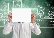 Uomo d'affari che tiene cartello in bianco davanti al suo fronte contro gli edifici per uffici disegnati a mano nel backgr immagini stock