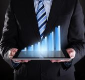 Uomo d'affari che tiene compressa digitale con il grafico Immagini Stock