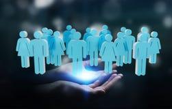 Uomo d'affari che tiene 3D che rende gruppo di persone in sua mano Immagine Stock Libera da Diritti