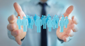 Uomo d'affari che tiene 3D che rende gruppo di persone in sua mano Fotografia Stock Libera da Diritti