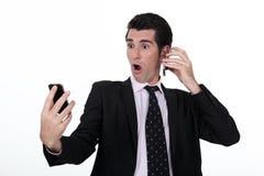 Uomo d'affari che tiene due telefoni cellulari Fotografia Stock Libera da Diritti